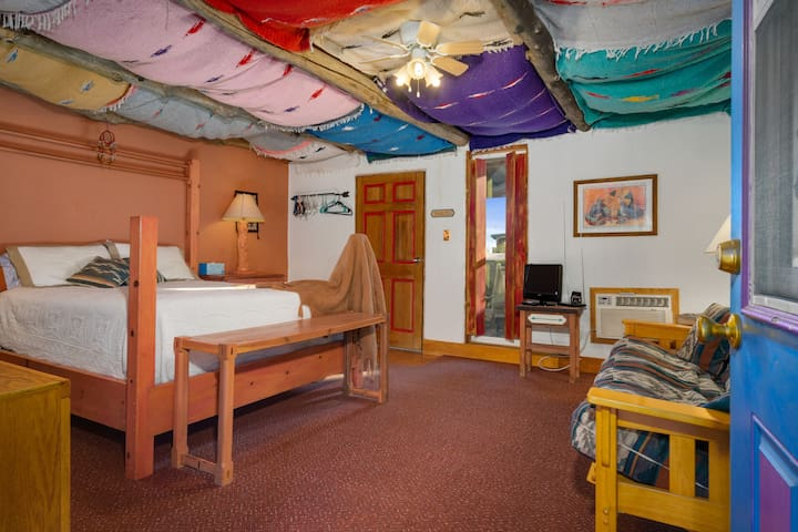 The rugs on the ceiling create a warm and cozy atmosphere.  The room has a heating/cooling unit and small TV.
