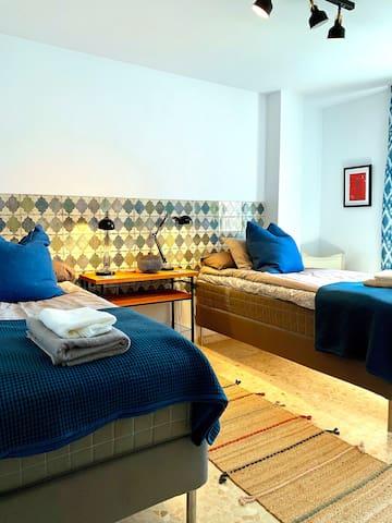 Sovrum med en blandning av industriell design och varma blåa toner. Bekväma continentalsängar. Uttag för usb.