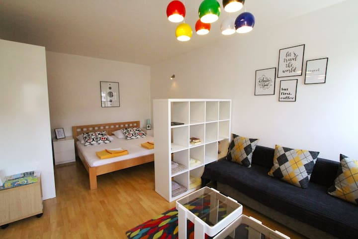 """Colorful and spacious bedroom with sofa and 43"""" smart TV"""