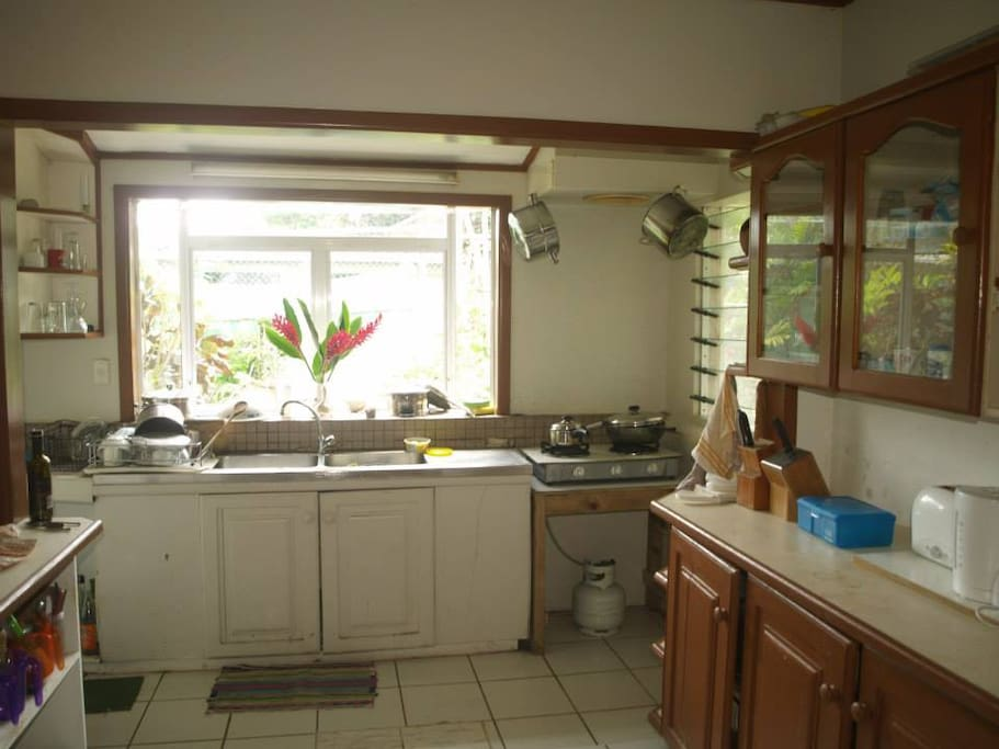 Large kitchen with gas cooker, Pantry storage, and fridge.