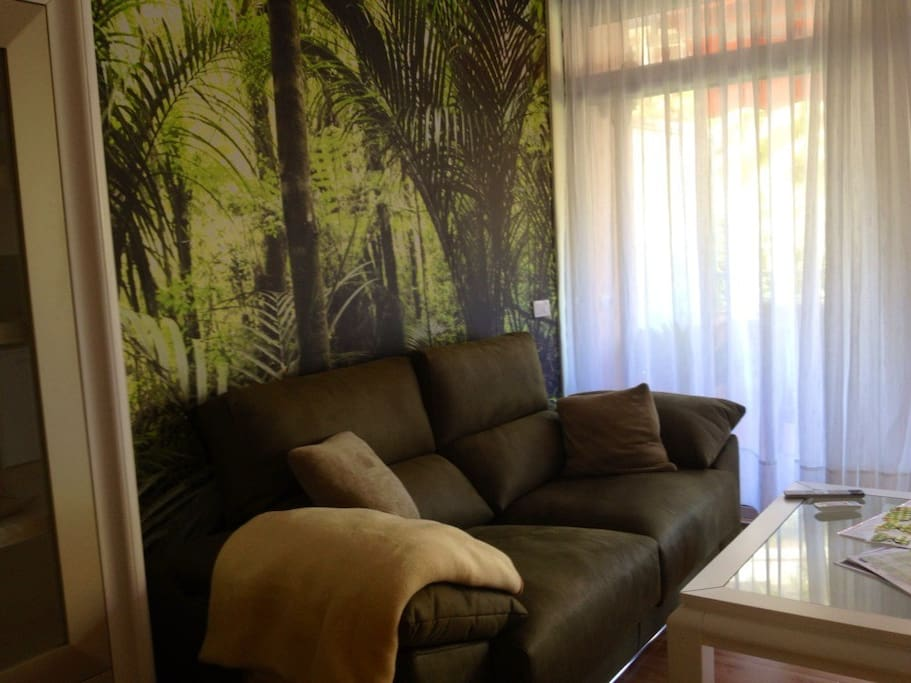 Das elegante und bequeme Sofa neben der großen Glasschiebetür  zur Terrasse