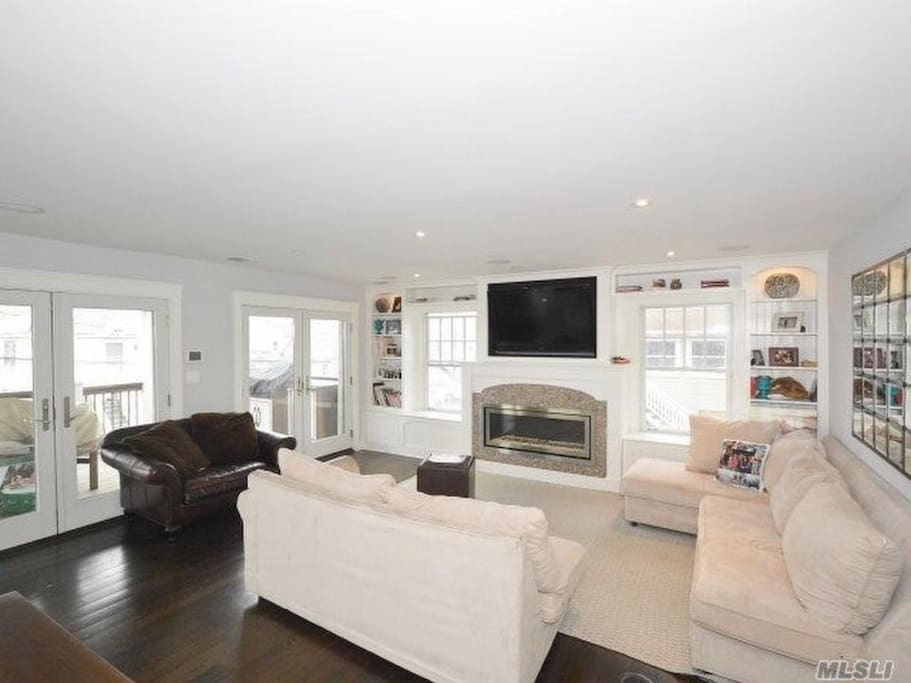 Living room with Built in TV over fireplace, radiant double plank wood floors