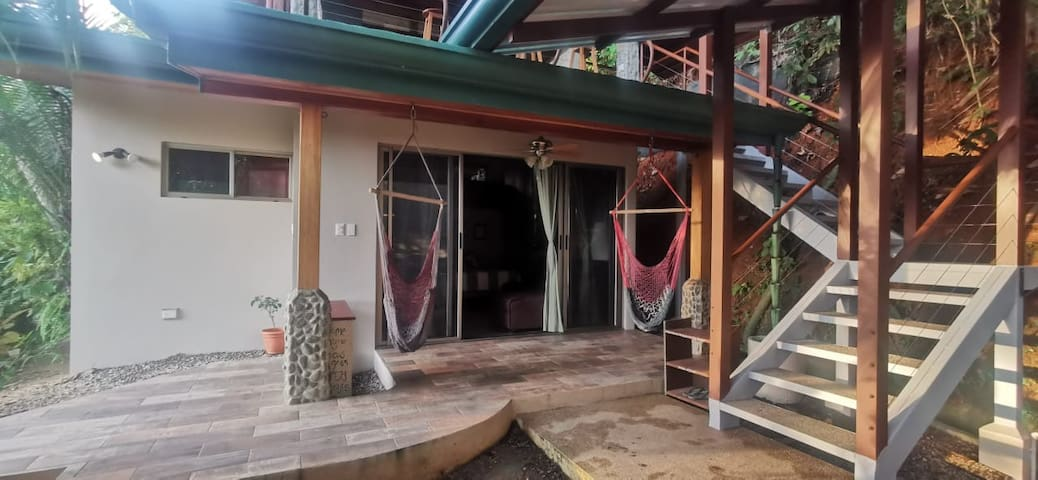 Fully covered patio with two hanging chair hammocks to laze away the day. Stairs to the right are fully covered as well and lead up to the private and complete kitchen and second sitting area.