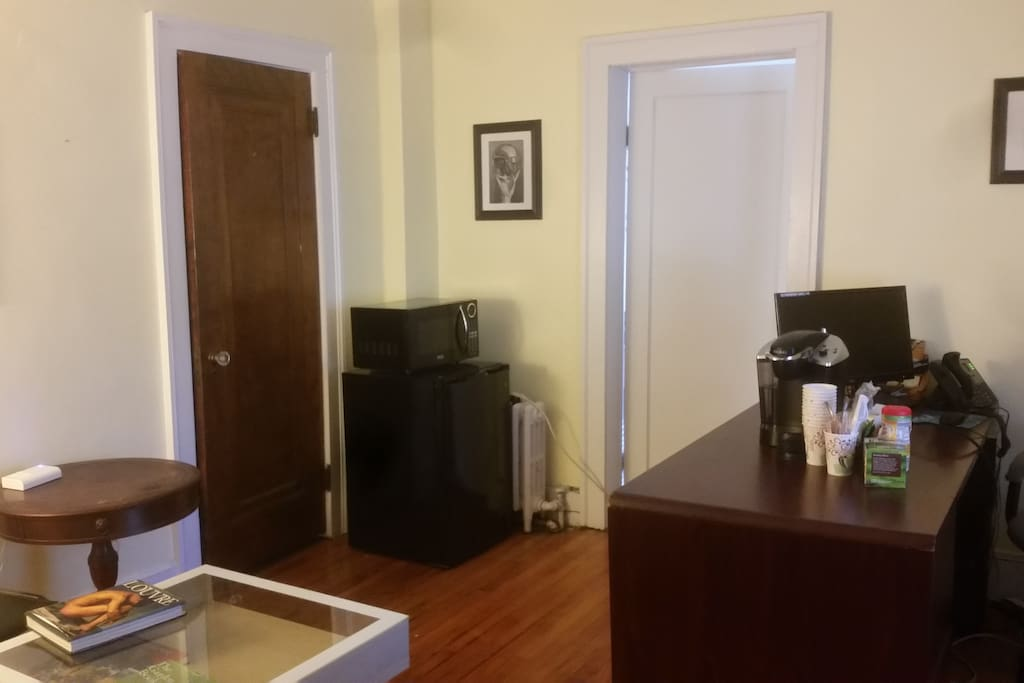 spare room with mini fridge, microwave, krups machine, iron & board