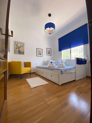 Chambre jaune avec un lit 160 x 200 et une armoire