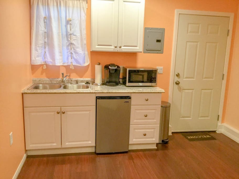 Mini kitchen with mini refrigerator, new microwave, Keurig coffee maker, sink, and dishes for your use in the cabinet drawers. Also has sink.