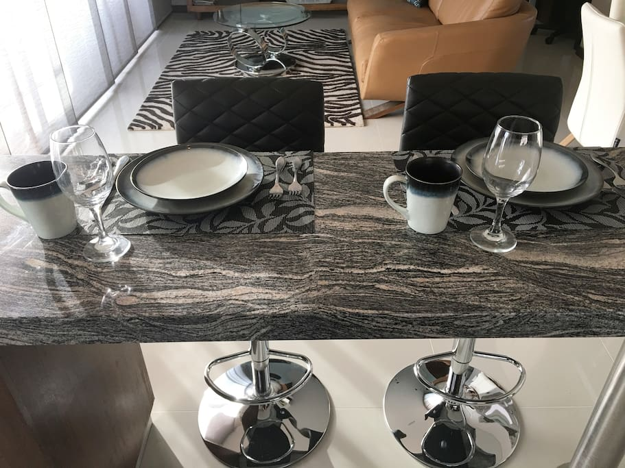 Bar set up for a meal!  Full dish set, wine glasses.  Lovely black and white stone/marble counters.