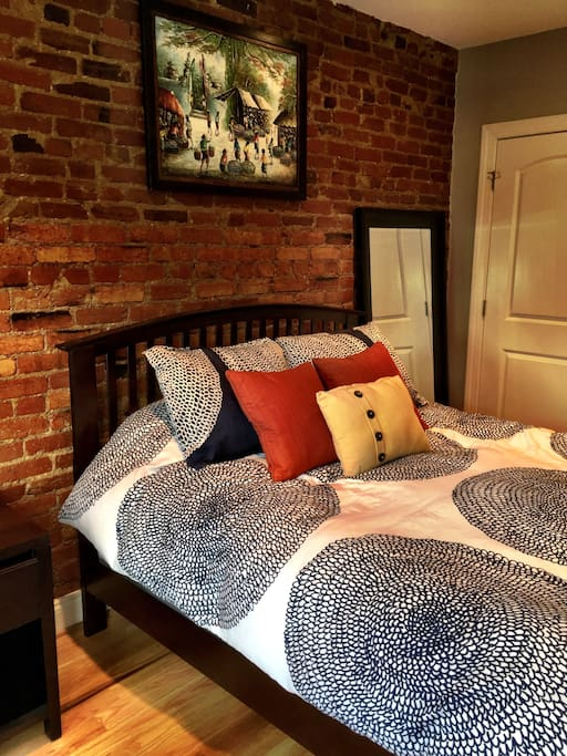 View of bedroom from windows featuring exposed brick
