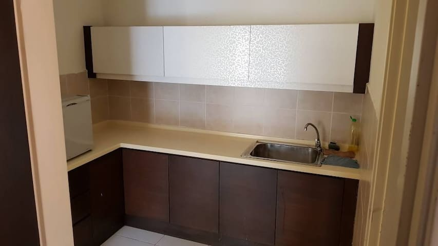 Kitchen with mini fridge, kettle jug , 4 mineral water, dish rack, dish washing liquid plates, forks and spoons