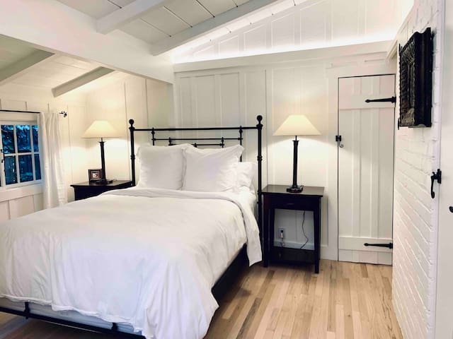 Cozy, en suite bedroom with vaulted ceilings and Restoration Hardware furniture and linens.