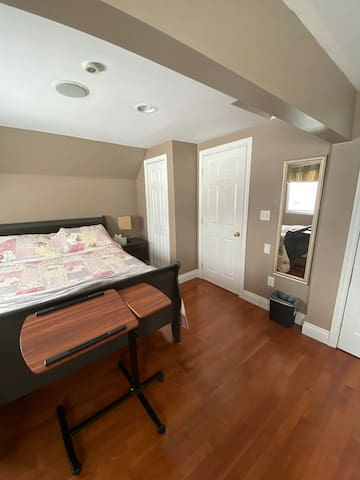 This queen-size bed is very comfy. In this room are a large double closet and a single closet, long sparkling clean mirrors, and a tall dresser. The Smart TV sets on the dresser.  The rolling tray you see in this picture is a laptop cart.