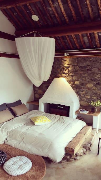 房间一:双人大床房,配有电子壁炉。裸露的石头墙