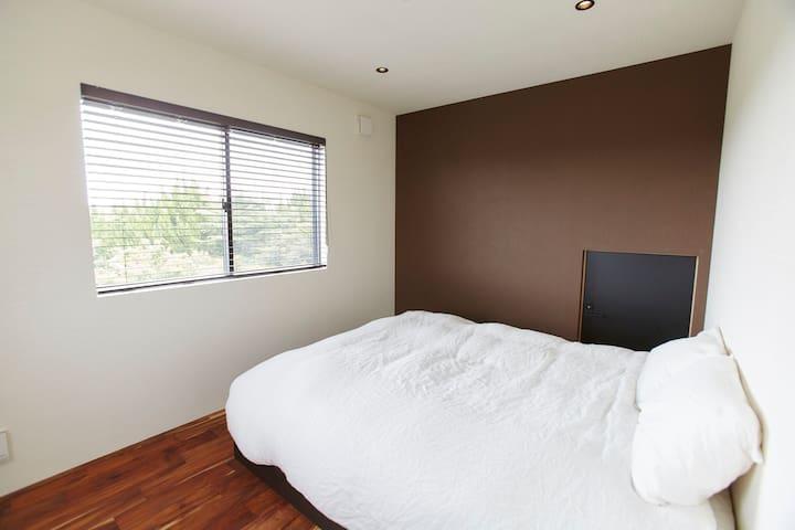 寝室1 クイーンベッド1台 プロ仕様のマットレスを厳選 天気が良い日は防風林の間から海が少し見えます