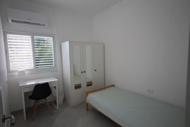 Chambre avec 2 lits simples et espace de travail dedie