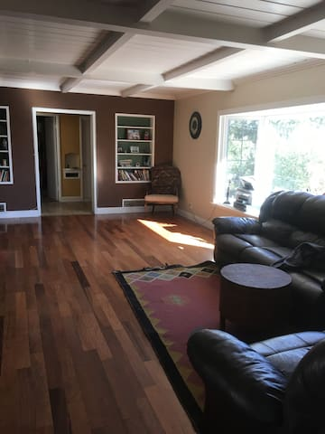 SHARED living room with sofa, loveseat, and wide open wood floors for additional floor mattress.