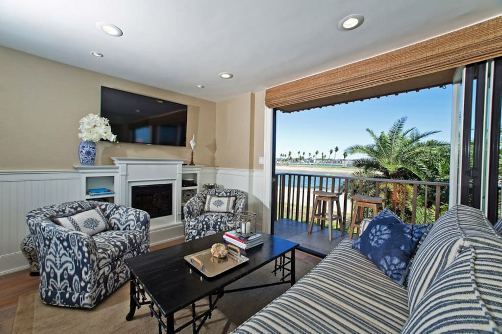 Living room with cable TV, fireplace and bay front patio
