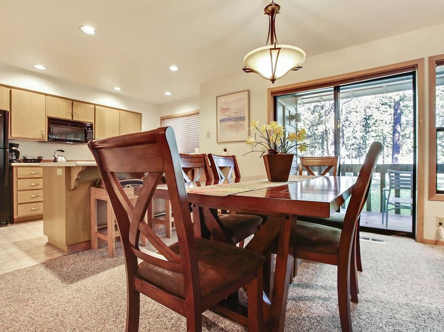 Dining room with 6 person table and 2 stools under counter