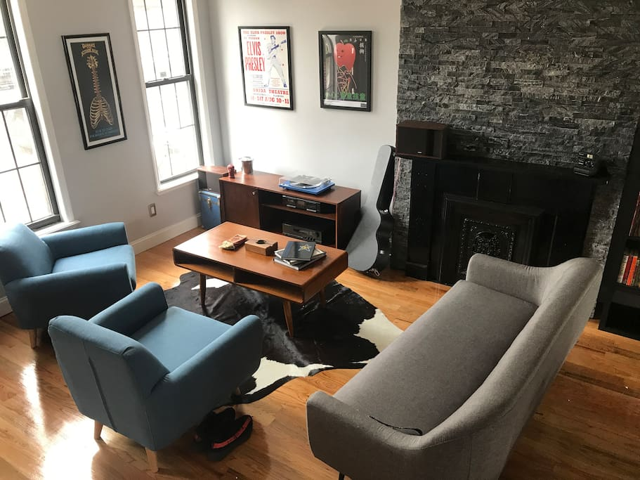 Living room has plenty of seating as well as a stereo equipped with a turntable and cassette deck as well as plent of music to choose from.