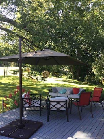 Terraza principal gratamente equipada con vista al jardín y arboles nativos.