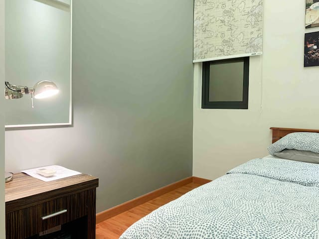 Aircond room with single bed, side table and a wardrobe.