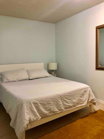 The bedroom includes a super comfy queen bed for two. The bed is always made with fresh, clean bedding and four pillows. The room also has a large mirror, ottoman, and a hanger for your clothes and shoes. The bedroom is quaint and comfortable.