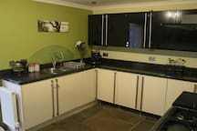 Kitchen with coffee machine and fitted dishwasher and washing machine.