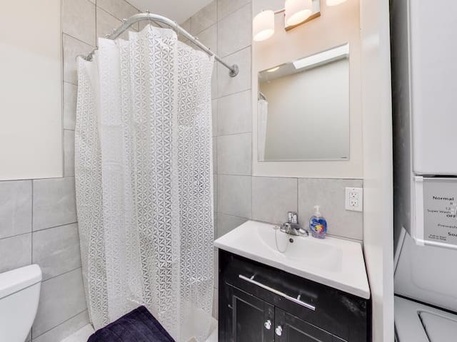 Modern bathroom with stand-up shower (no bathtub) and stacked clothes washer and dryer.