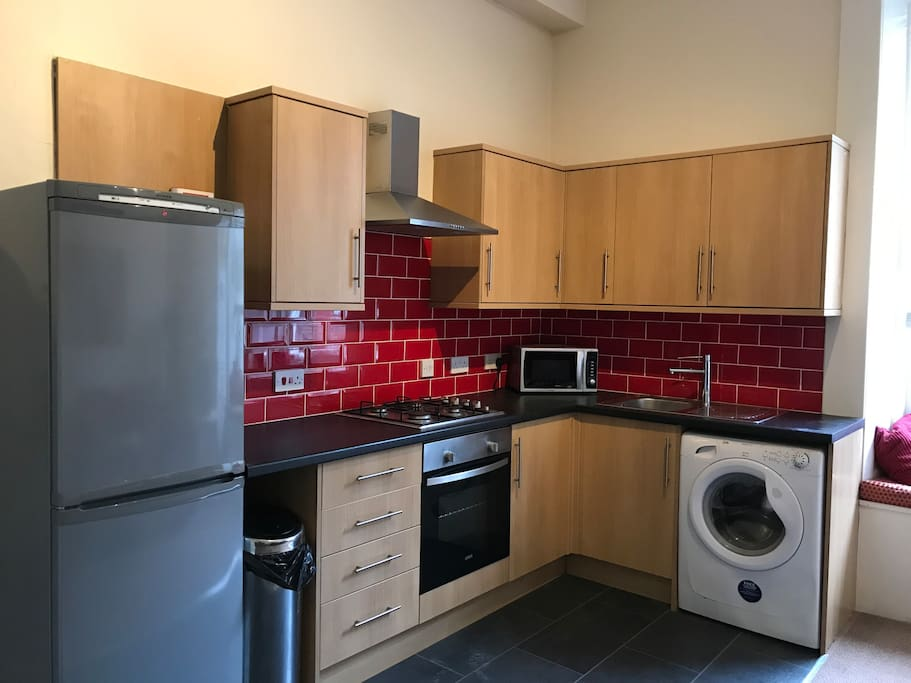 Kitchen with a gas hob, electric oven, large fridge freezer and a washing machine.