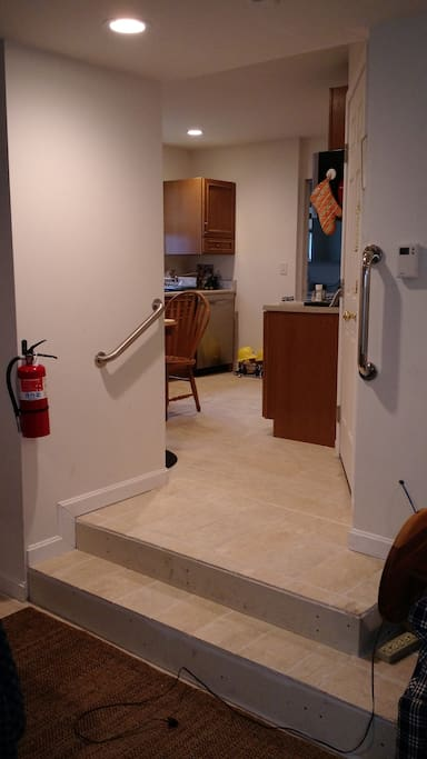 Just a two steps up from bedroom to kitchen, bath and sunroom. Grab bars on both sides of stairs.