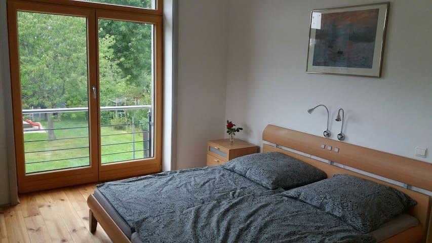 Schlafzimmer mit Doppelbett und mit großem Fenster zum Garten hin