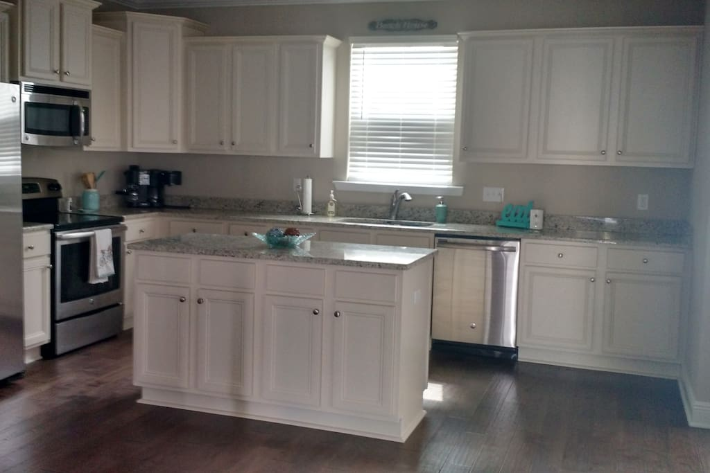 Huge open kitchen with all cooking supplies including pots, pans, toaster, coffee pot, plates, utensils, etc.