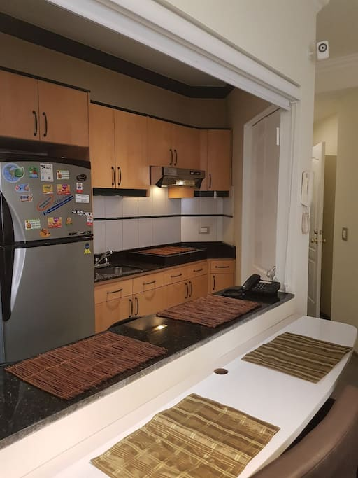 Mini cocina con desayunador. Microondas, refrigeradora y cocina.