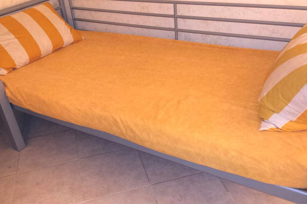 the master single bedroom with a thin mattress and slatted