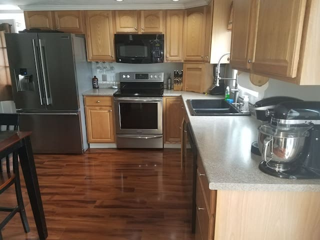 Commercial size refrigerator, glass top stove, microwave, dishwasher, and fully supplied kitchen.