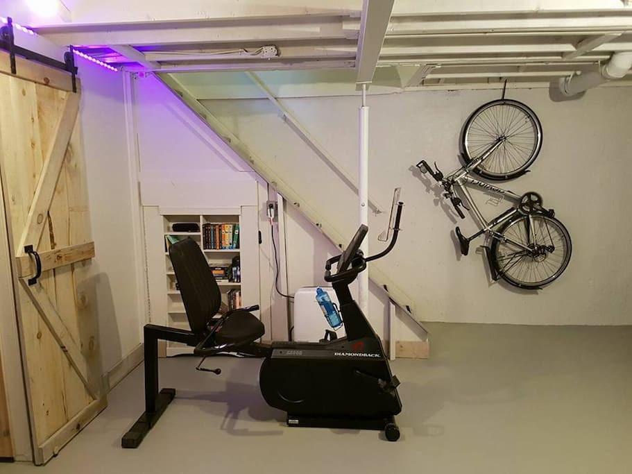 The basement gym includes light free weights, a recumbent bicycle, and an elliptical. There is also a large TV and a ping pong table.