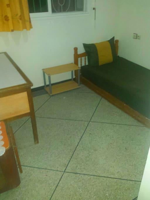Une petite chambre qui se compose d'un bureau.,un placard, un lit et une comode