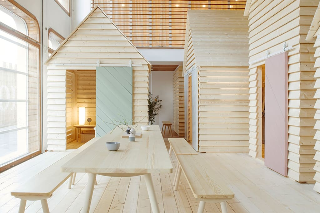 """KOTI (Finnish for """"home"""") transforms the Institut finlandais to bring the magic of the communal cottage experience to Paris's Rive Gauche. Each evening, up to 12 guests can book from a selection of six spruce timber aitta. Each day, the installation is open for the public to visit."""