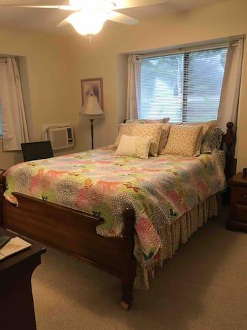 Master Bedroom W Queen Bed, en suite bathroom, TV, fan and wall air conditioner.