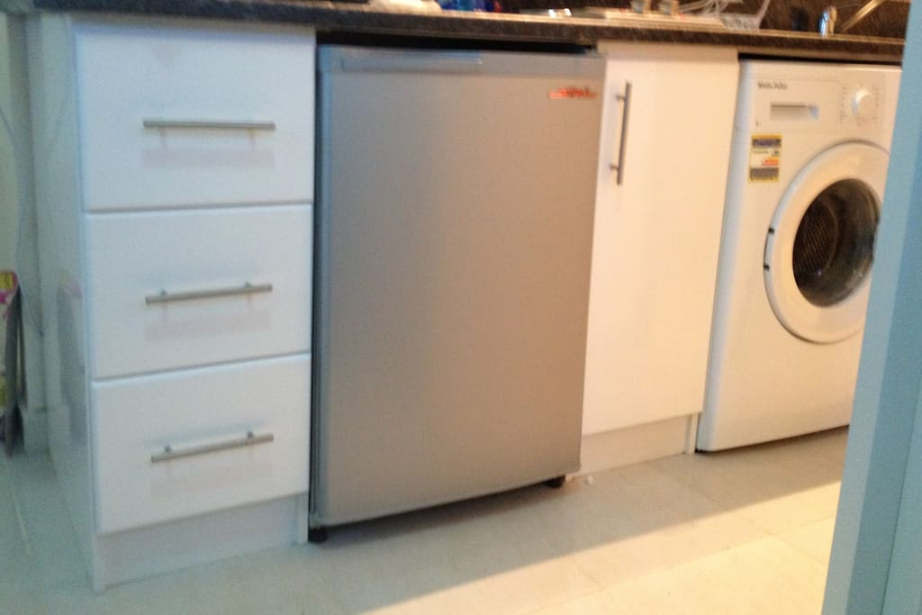 Nicely appointed kitchen with clothes washer.