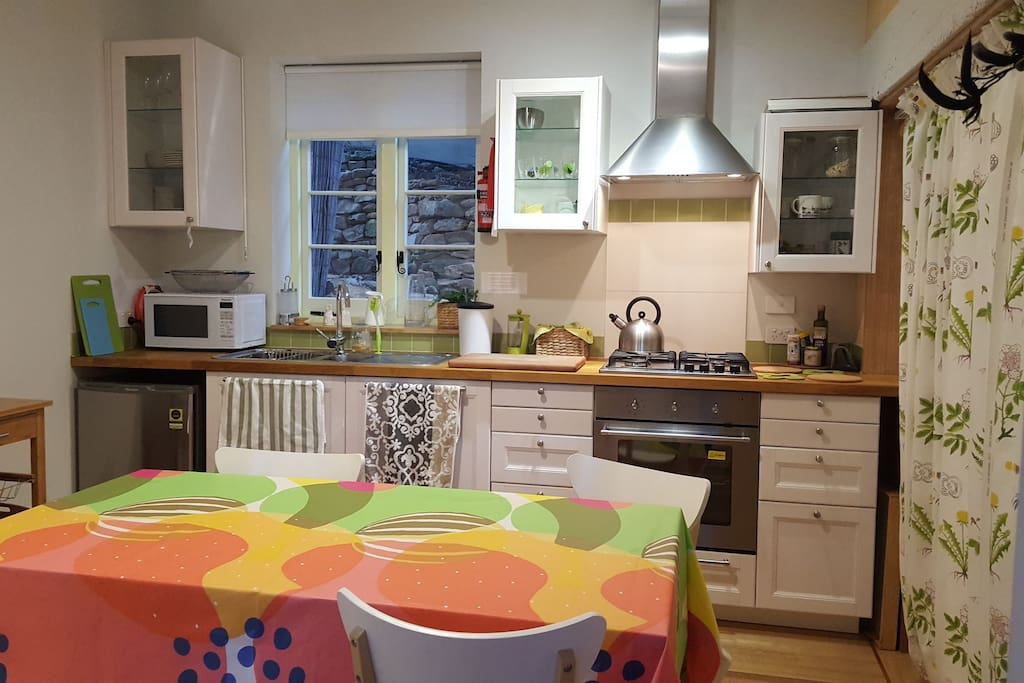 Well equipped kitchen with dishwasher and place settings for 4