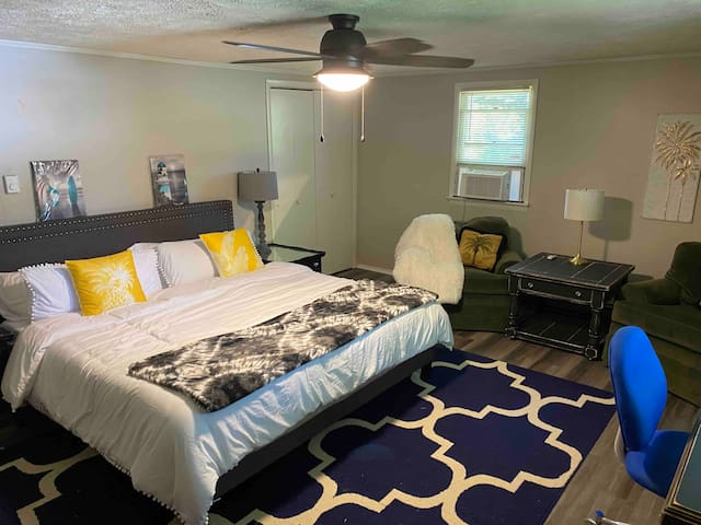 Large master bedroom with king bed, extra seating and a desk