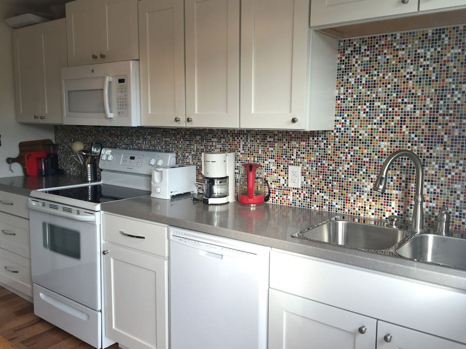 The kitchen has lots of dishes, glasses, cutlery, and cookware