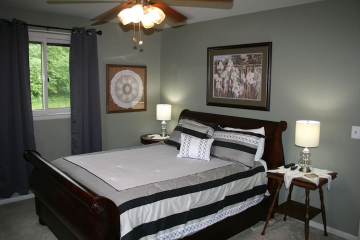 First large bedroom with comfortable queen size sleigh bed, black out window treatments.