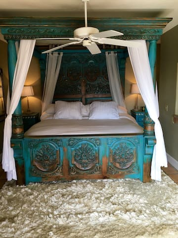 Master king bed with turquoise canopy.