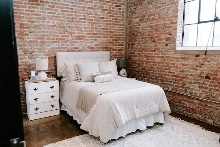 """This standard bed welcomes you to the bedroom which is truly in """"The Corner""""-bordered by both original brick walls of the warehouse"""