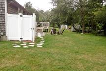 Back yard with outdoor shower, space for games, fire pit and seating