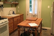 Kitchen with island for counter space. Door to back area of home.