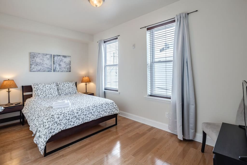 Large bedroom with a closet, smart TV, dresser and luggage rack.