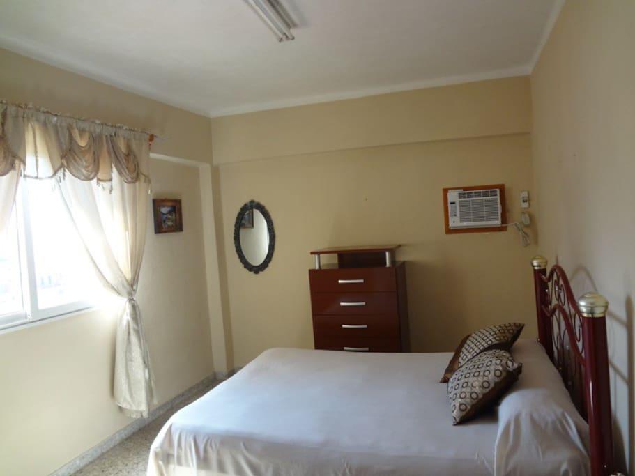 Habitación 1. Tiene una excelente iluminación y ventilación natural, al punto de que muchos huéspedes no encienden el aire acondicionado. Está habilitada además con una cama matrimonial, gavetero, closet y nevera.