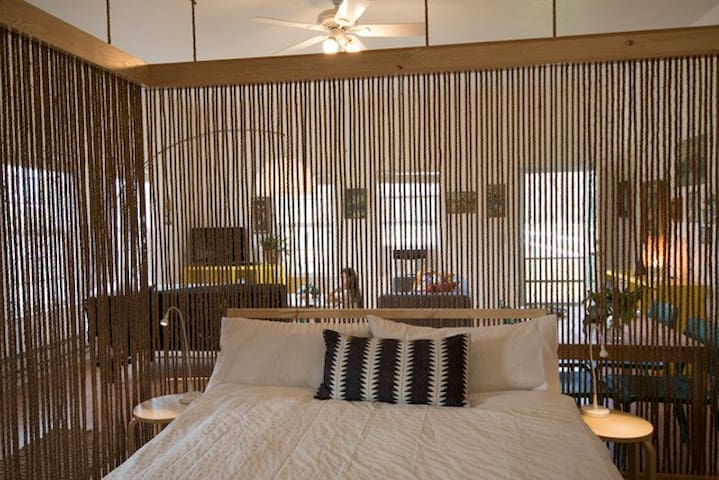 Bedroom area is separated from the rest of the space with a divider made of rope and wood.